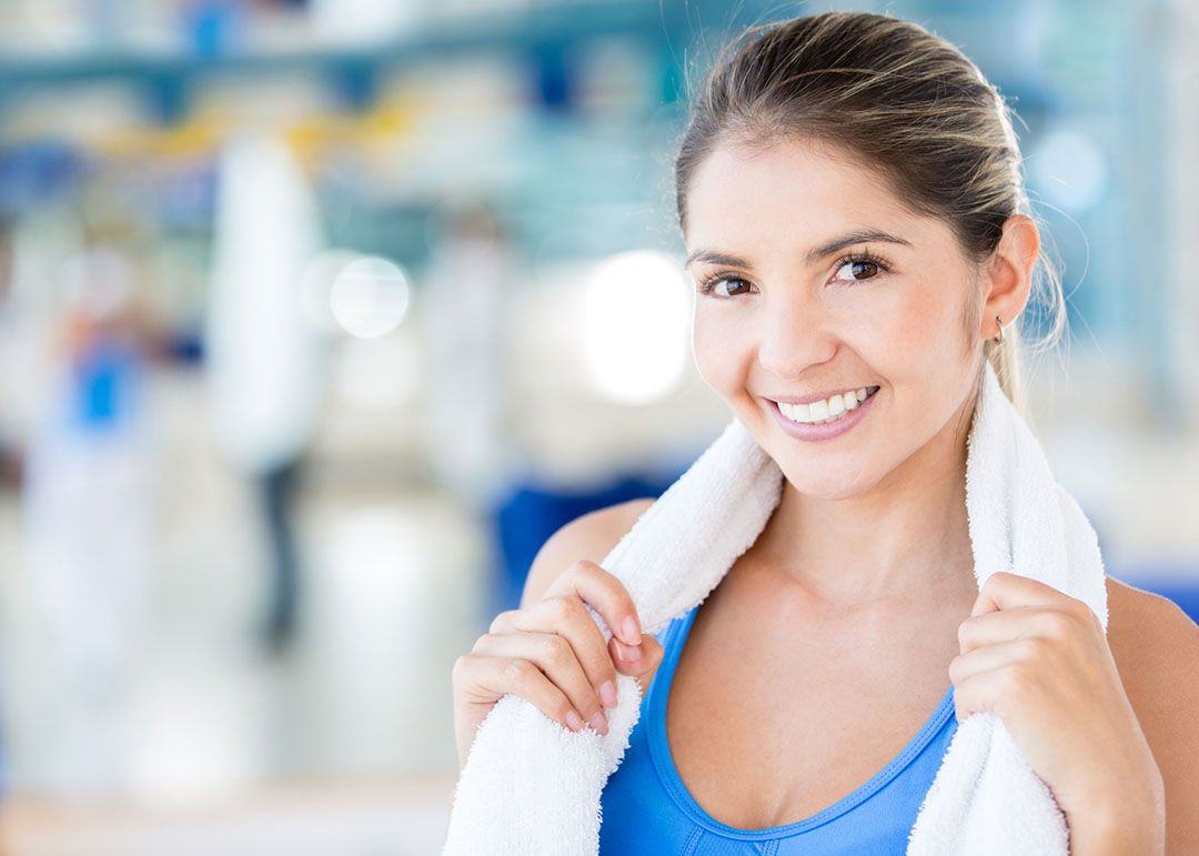 Beautiful woman at the gym holding a towel and looking happy