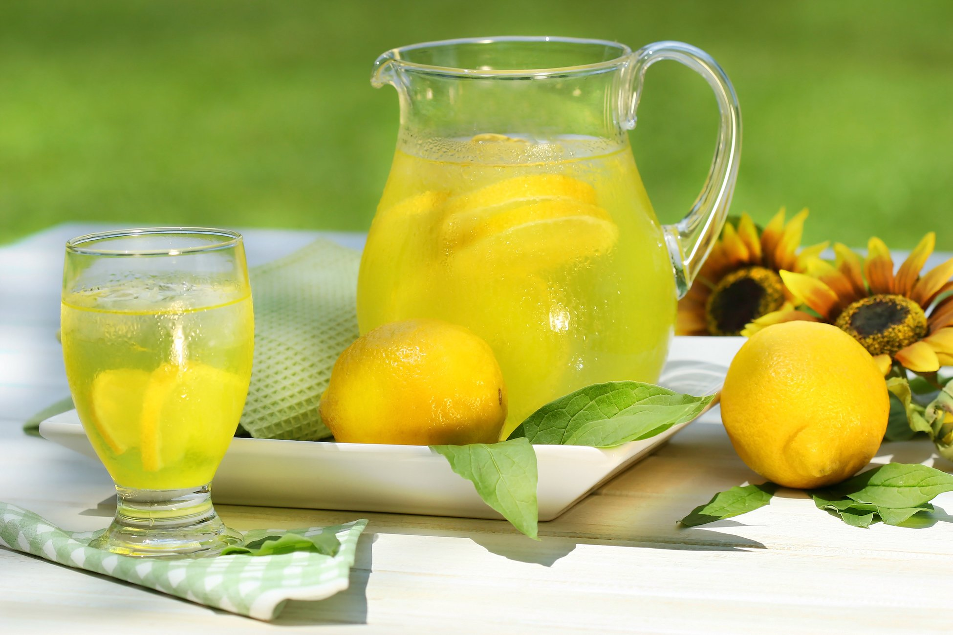 Pitcher of cool lemonade with glass on table