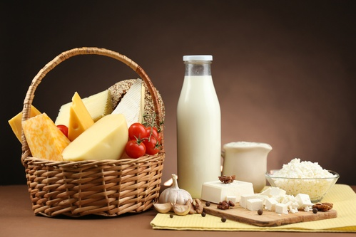 Basket with tasty dairy products on wooden table, on dark brown background