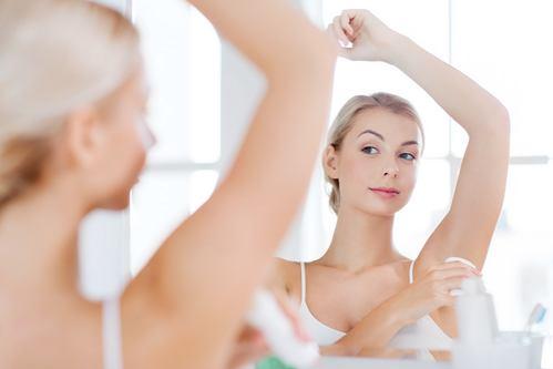 woman with antiperspirant deodorant at bathroom