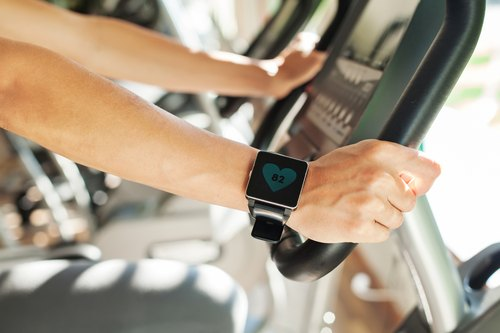 Smart watch showing a heart rate of excercising woman in gym