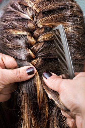 Hairdresser braiding a clients hair