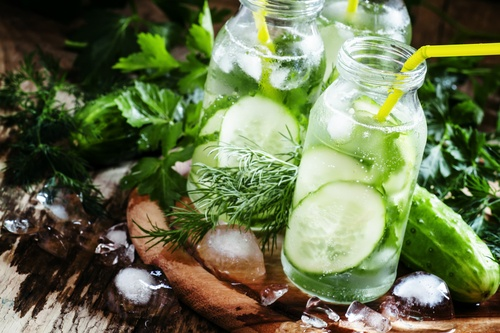 Cucumber fizzy drink with herbs and ice , selective focus