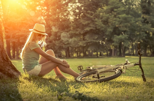 Woman sitting under sun light at day near her bicycle in the par