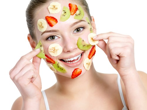 Happy woman with fruit facial mask