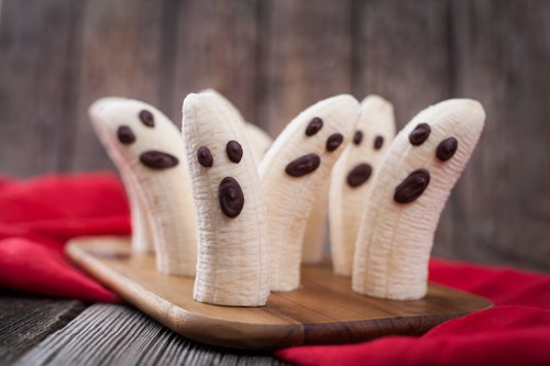 Homemade halloween scary banana ghosts monsters with chocolate faces. Healthy natural vegetarian snack funny dessert recipe for party decoration on vintage wooden table background and red fabric