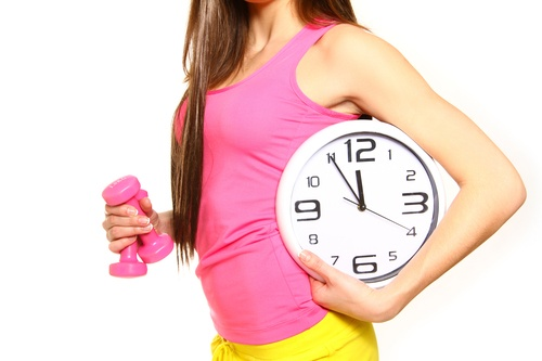 Athletic young woman with a clock and dumbbells on a white background