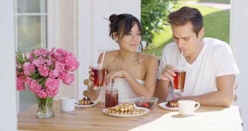 Couple drinking iced tea at breakfast outside
