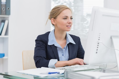Young business woman working on computer at desk in office