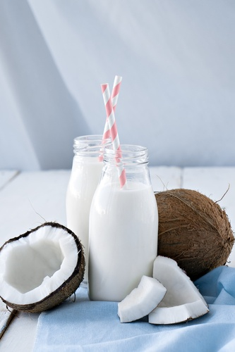 coconuts with coconut milk on wooden table