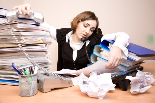 Young businesswoman with tons of documents