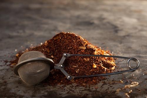 Rooibos Tea and tea-strainer on a metal texture