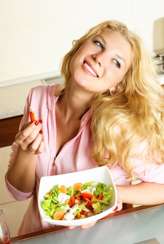 Pretty girl eating salad