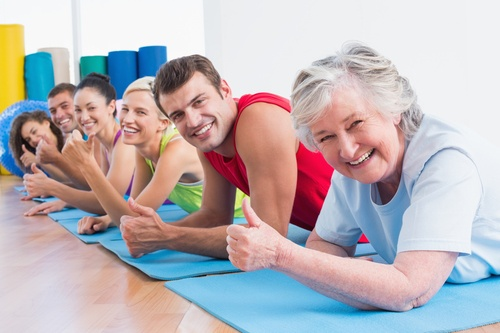 Portrait of happy senior woman with friends gesturing thumbs up while lying on exercise mats at gym