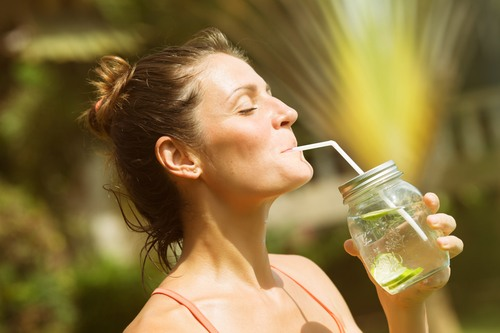Woman drinking water detox dressed in sports clothes