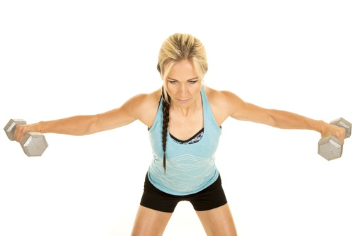 woman in a blue fitness tank top working shoulders