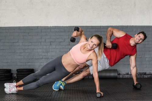 Fit couple doing dumbbell rows in crossfit gym