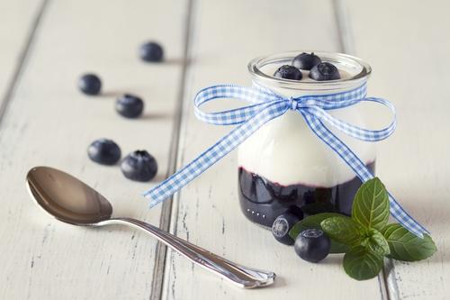 Jar with greek yogurt, blueberries jam in a white wooden table
