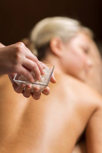 close up of woman having salt massage in spa