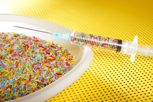 Little colorful candy syringe over yellow background