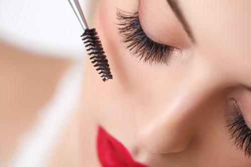 Woman eye with beautiful makeup and long eyelashes. Mascara Brus