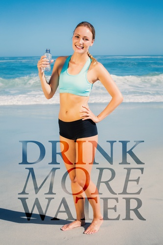 Fit woman standing on the beach holding water bottle against drink more water