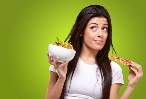 portrait of young woman choosing pizza or salad against a green