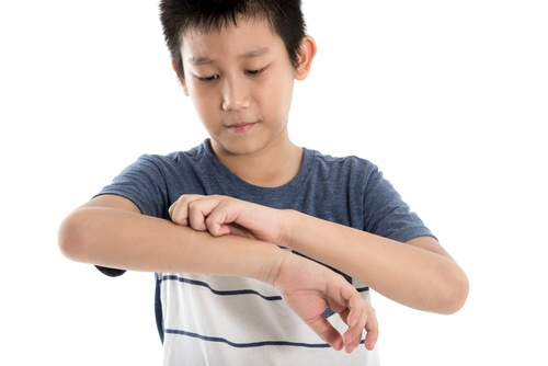 Asian boy scratching his arm on white background.