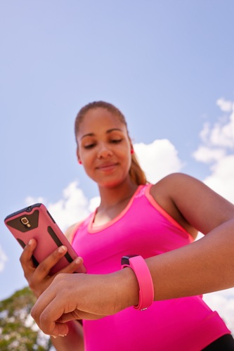 Woman Syncronizes Fitness Watch Fitwatch With Phone