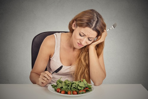sad displeased young woman eating salad