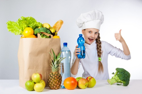 Little happy girl in a cap cook a variety of fresh food. A girl holding a bottle of pure mineral water for cooking healthy meals. A girl holds a finger up.