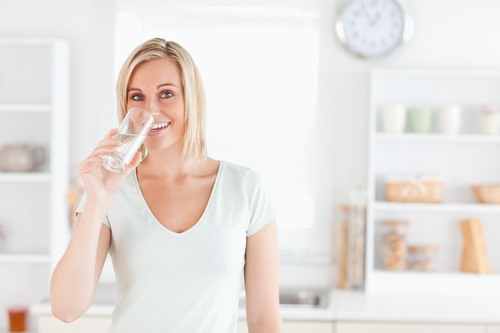 Charming woman drinking water while standing looks into camera