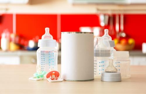 Feeding bottles with bank of baby milk formula on kitchen background